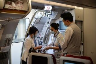 7点20分,海南航空HU7181航班开始迎接旅客登机,乘务员指引旅客入座(摄影:宁隆宇)