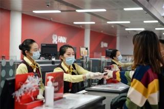 在海口美兰国际机场,海南航空的地服人员正在为旅客办理值机手续(摄影:宁隆宇)