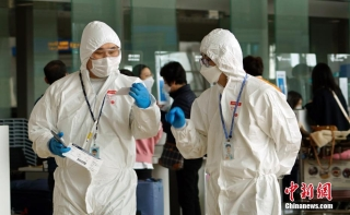 当地时间3月4日,韩国仁川机场内工作人员身着防护服。中新社记者 曾鼐 摄