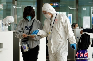 当地时间3月4日,在韩国仁川机场,航空公司工作人员检查旅客防疫证明等。 中新社记者 曾鼐 摄